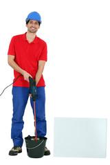 Tradesman using a screw gun with an attached mixer