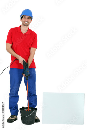 Tradesman using a screw gun with an attached mixer
