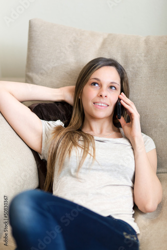 Woman sitting on the sofa at home while talking on phone
