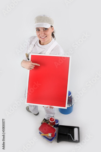 Painter holding a blank red sign