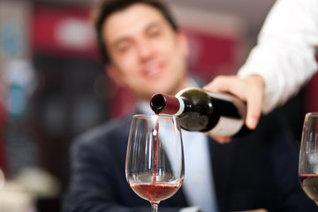 Waiter pouring red wine to a man