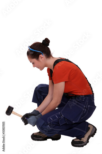 Woman kneeling with mallet