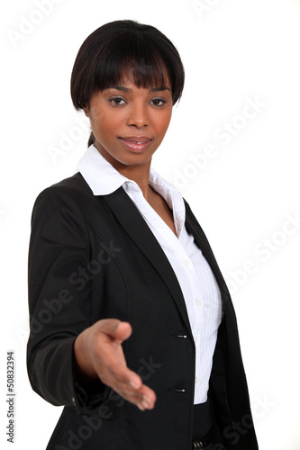A businesswoman about to shake hands.