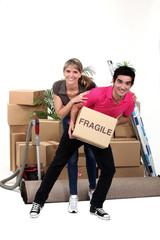 Playful couple moving house