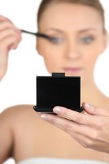 Woman applying mascara looking at a compact mirror