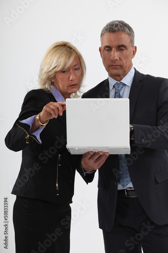 Mature businessman and businesswoman in front of computer