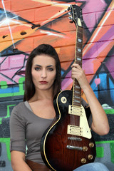 Woman with guitar in front of painted wall