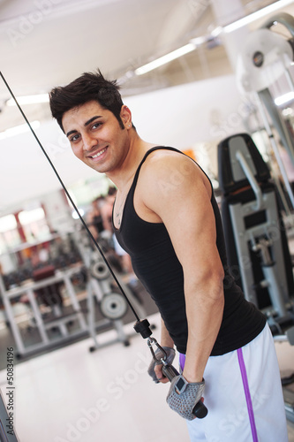 Young smiling man training in the gym.