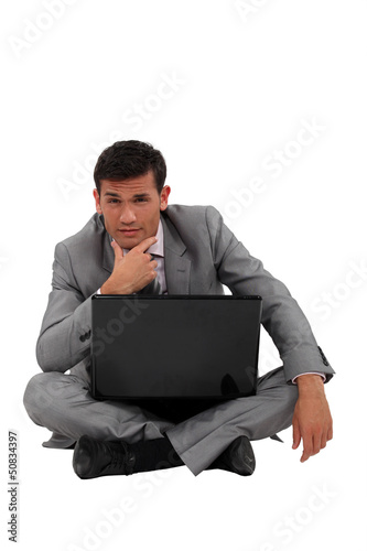 Pensive businessman sat on floor with laptop