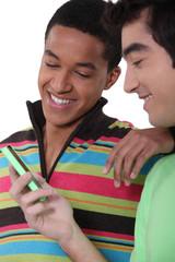 Teens looking at mobile phone screen