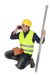 Builder holding a girder while talking on the phone