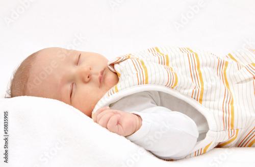 Leinwanddruck Bild Sleeping baby on back in sleeping bag