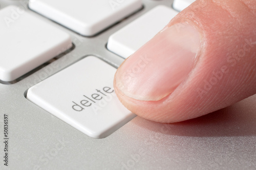 Finger pressing a DELETE key