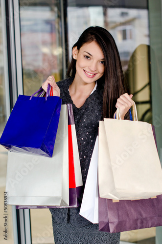 Beautiful girl holding many shopping bags in front of the mall.