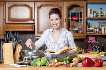 beautiful housewife cooking vegetables with cookbook