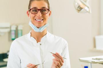 Zahnärztin in Ihrer Praxis hält Spiegel und Kratzer