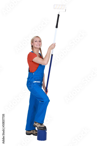 Woman with an extended paint roller