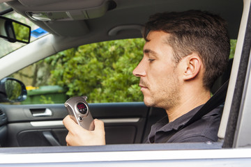 Man looking at breathalyzer