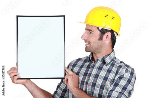 young helmeted blue collar in profile holding copyspace
