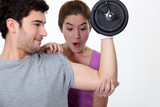 Amazed woman looking at her boyfriend's new muscles