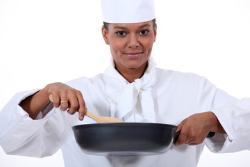 Woman chef stirring a wok