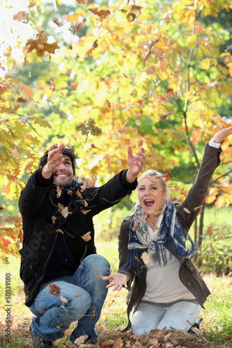 joyful couple playing with dead leaves in autumn