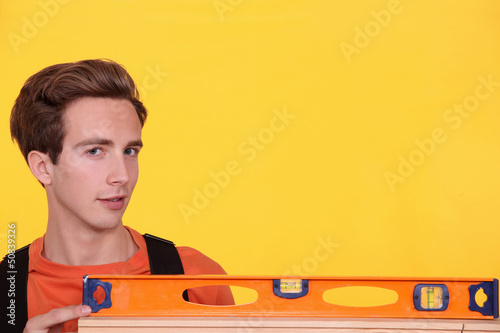 Man with spirit level on yellow background