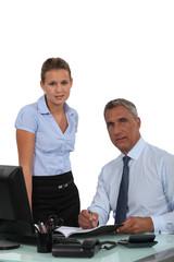 Secretary making boss sign paperwork
