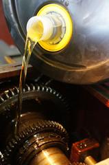 A mechanic pours fresh oil into a car