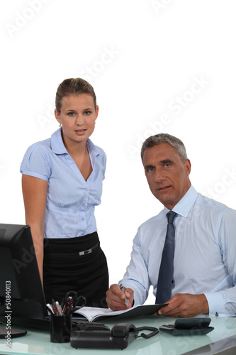 Secretary making boss sign paperwork