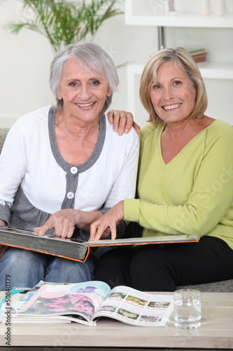 Mother and daughter looking through photo album