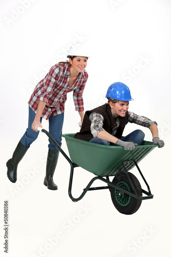 Two female construction workers racing in a wheelbarrow.