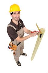 Carpinter measuring plank of wood