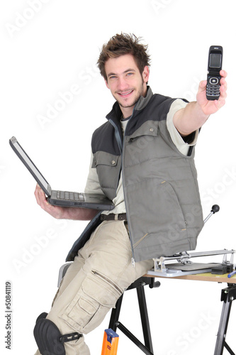 Tradesman holding a mobile phone and a laptop