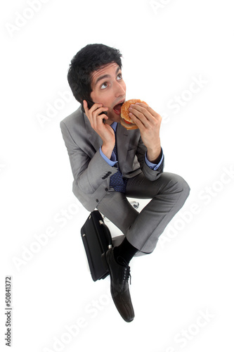 Businessman on the phone eating hamburger