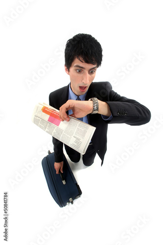 Stunned businessman looking at the time