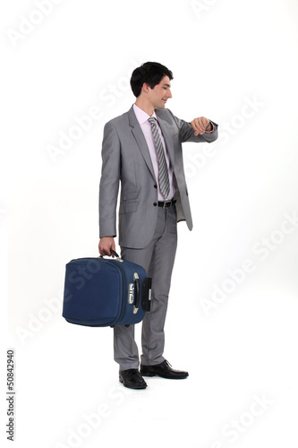 businessman with luggage consulting his watch