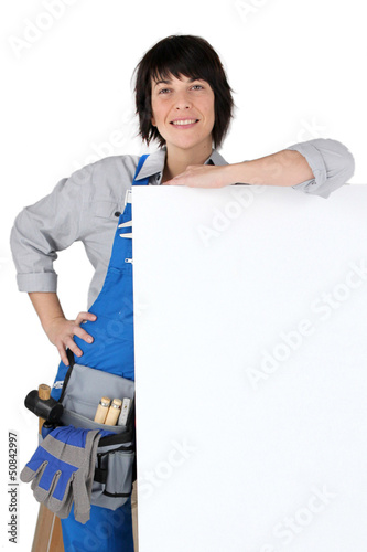 Female carpenter with a board left blank for your message