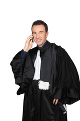 University don in graduation robes on cellphone