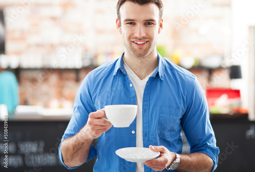 Man holding cup of coffee in cafe