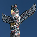 A totem wood pole in the blue cloudy background