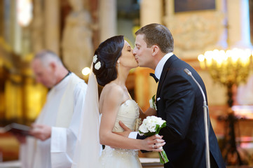Bride and groom kissing in a church