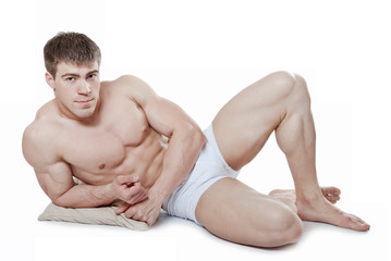 An attractive young man, lying on a cushion