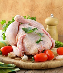 fresh raw chicken on a cutting board with vegetables and herbs