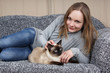 happy young woman with siamese cat