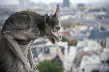 Stone gargoyle overlooking Paris from the Notre Dame