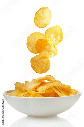 Potato chips falling in a bowl