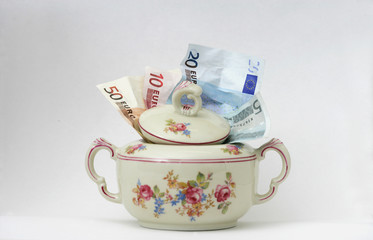 Verschiedene Geldscheine in einer bunten Zuckerdose