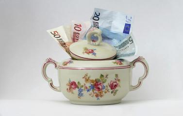 Geldscheine in Zuckerdose, Symbol für unattraktive Geldanlagen