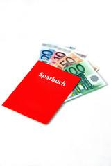 Rotes Sparkassenbuch, in dem sich Geldscheine befinden..